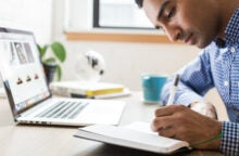 A young man writes in his notebook in front of an open laptop.